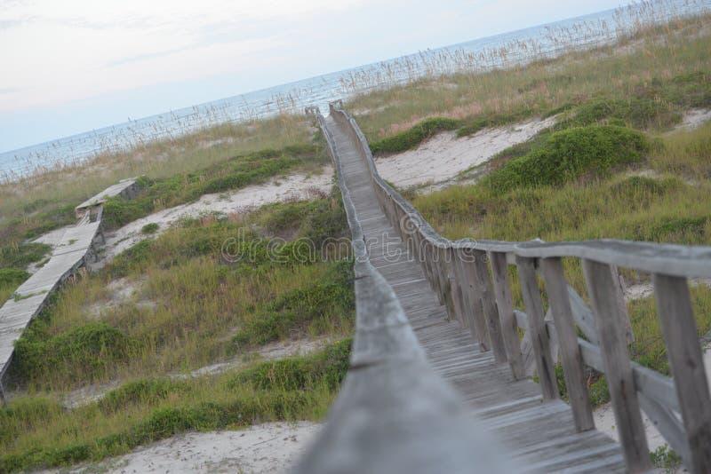 O caminho de madeira conduz à linha costeira arenosa do Oceano Atlântico foto de stock