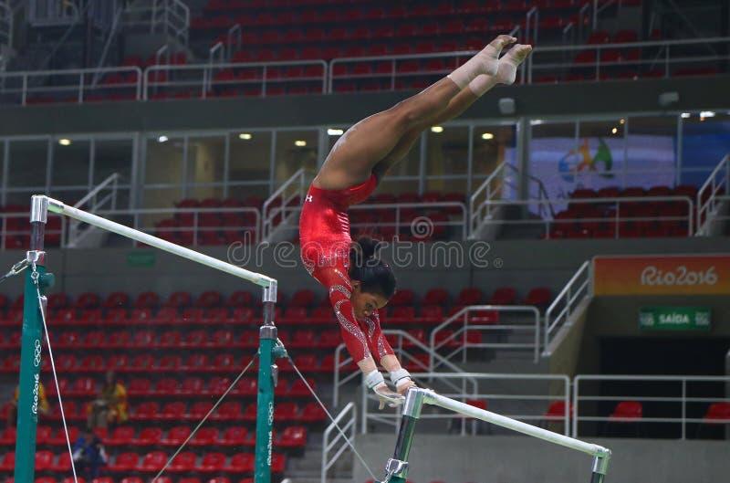 O campeão olímpico Gabby Douglas do Estados Unidos pratica nas barras desiguais antes da ginástica total do ` s das mulheres no R fotografia de stock