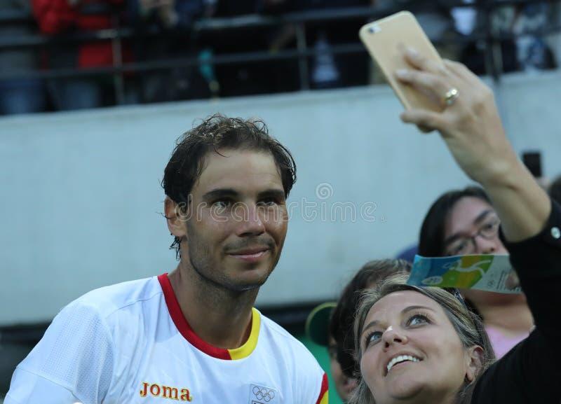 O campeão olímpico Rafael Nadal da Espanha que toma o selfie com o fã de tênis após o ` s dos homens escolhe o semifinal do Rio 2 imagens de stock royalty free