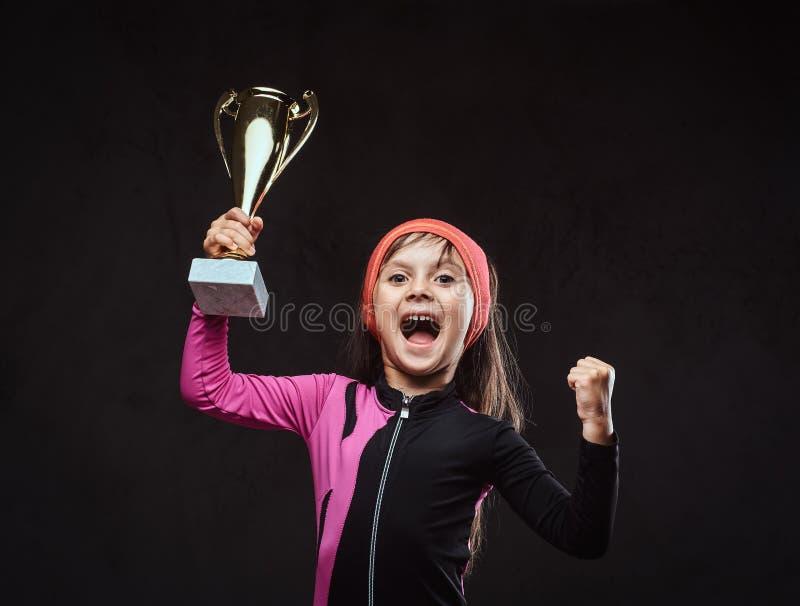 O campeão pequeno alegre da menina do skater guarda um copo do ` s do vencedor Isolado em um fundo textured escuro imagens de stock royalty free