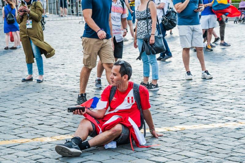 O campeonato do mundo 2018 de FIFA O fã peruano com as bandeiras do Peru e do russo senta-se no quadrado vermelho imagem de stock