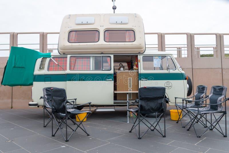 o campista Kombi do transportador da VW do estilo dos anos 60 estacionou na praia de Scheveningen fotografia de stock royalty free
