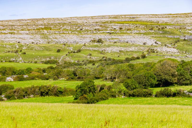 O campo de exploração agrícola e a montanha da rocha na maneira de Burren arrastam fotos de stock