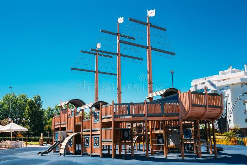 O campo de jogos da criança deu forma ao navio de pirata de madeira velho dentro fotografia de stock