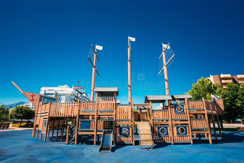 O campo de jogos da criança deu forma ao navio de pirata de madeira velho dentro fotos de stock