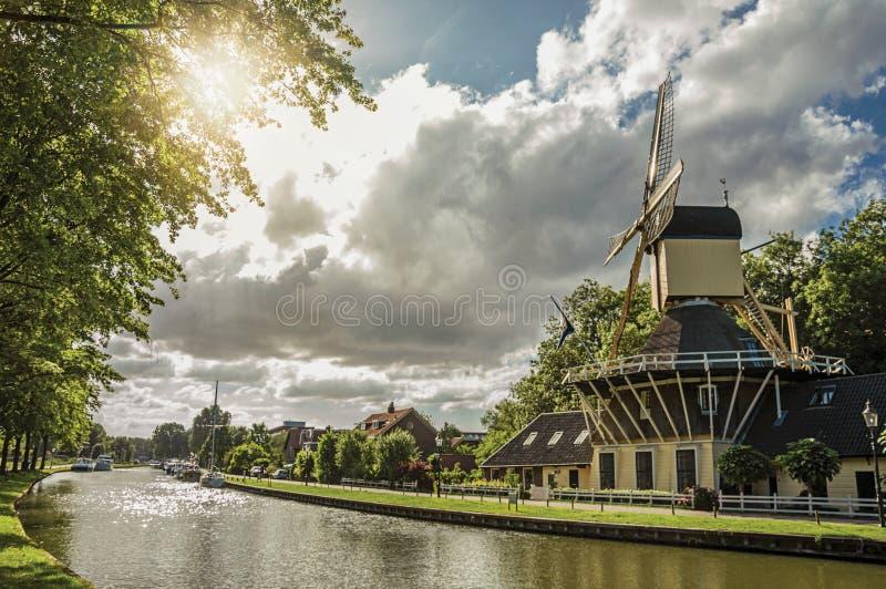 O canal árvore-alinhado largo com moinho de vento e barcos e brilho do por do sol refletiu na água em Weesp fotos de stock royalty free
