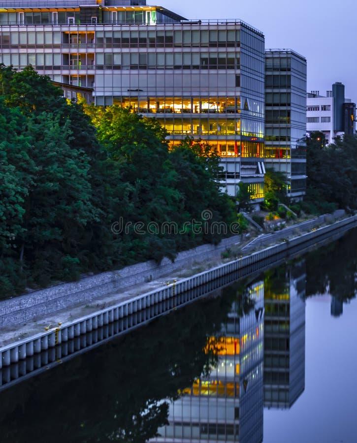 O canal de Teltow em Berlim-Tempelhof, Alemanha, com vista a um prédio de escritórios moderno Alguns assoalhos são coloridos ilum fotografia de stock