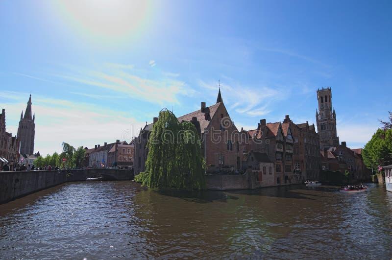 O canal em Bruges e a torre de sino famosa elevam-se no fundo em um dia de mola bonito foto de stock royalty free
