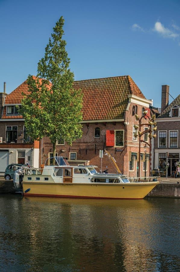 O canal largo com casas do tijolo, barcos amarrados em seu banco refletiu na água e no céu azul do por do sol em Weesp fotos de stock