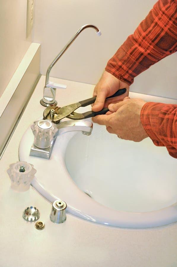 O canalizador aperta o faucet gotejante foto de stock royalty free
