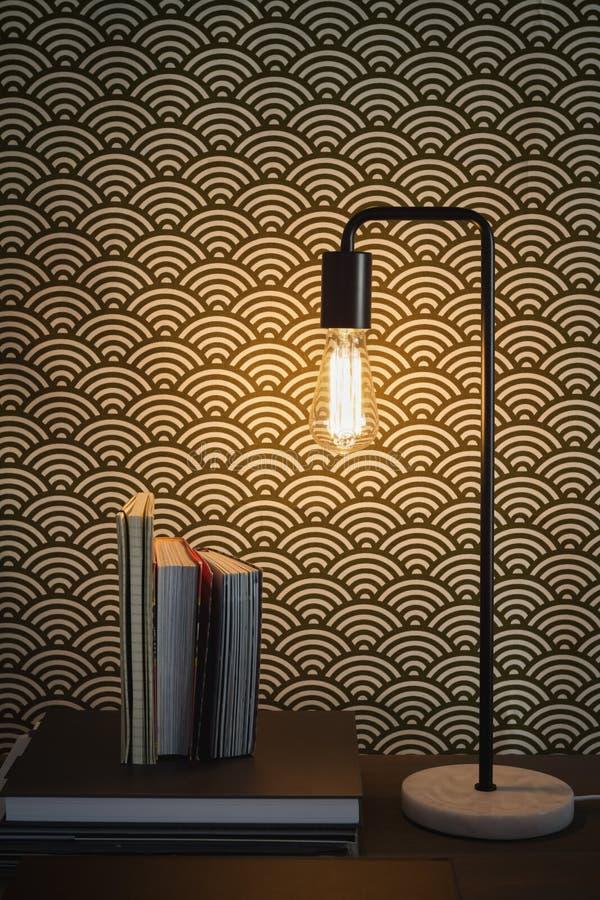 O candeeiro de mesa e os livros do filamento de Edison dirigem o interior fotografia de stock royalty free