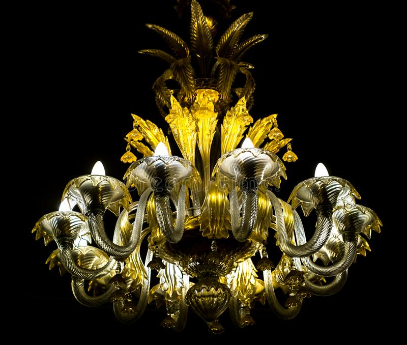 O candelabro de cristal brilha a suspensão do teto na obscuridade imagem de stock