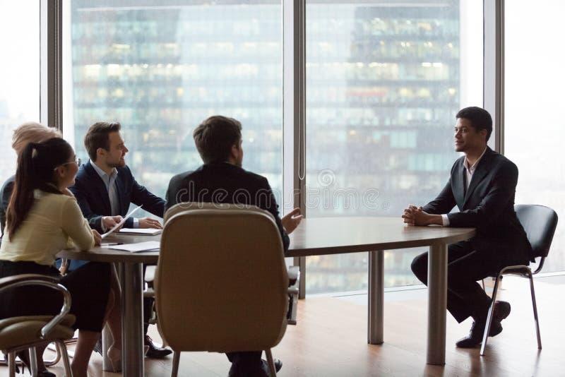 O candidato preto seguro imprime recrutas durante a entrevista imagens de stock royalty free