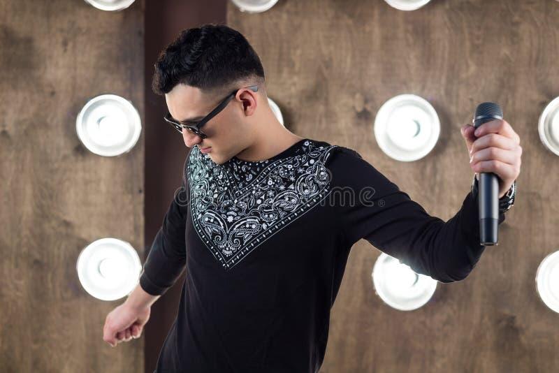 O cantor masculino do PNF executa na cena em luzes dos projetores foto de stock royalty free