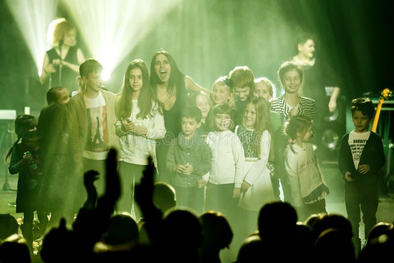 O cantor ucraniano famoso Jamala sorri com uma multidão de crianças fotografia de stock