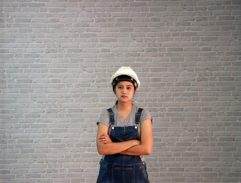 O capacete branco dos mercadorias da mulher do técnico com o avental cinzento das calças de brim do t-shirt e da sarja de Nimes v imagens de stock