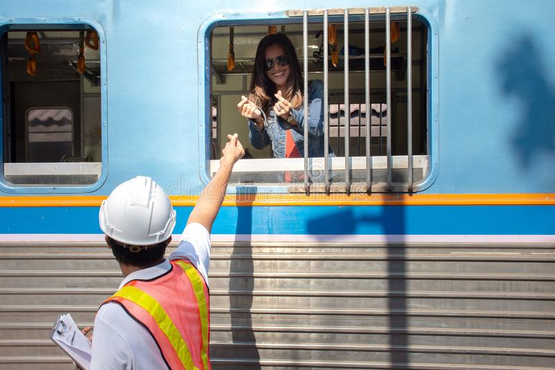 O capacete de segurança vestindo do coordenador asiático mostra o mini coração à amiga no trem imagem de stock