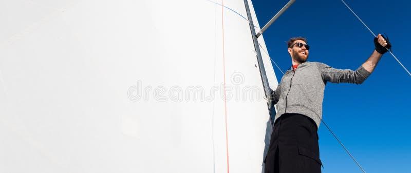 O capitão do iate com uma barba está no crescimento da vela em um iate de navigação, guardando a corda em sua mão e sorrindo, sen fotos de stock royalty free