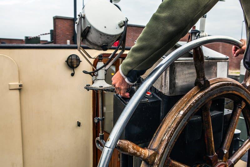 O capitão opera um volante antigo do navio fotos de stock