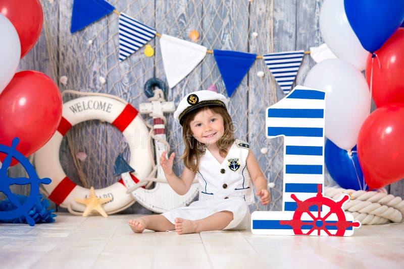 O capitão pequeno senta-se no assoalho em um estilo marinho Nós marcamos o primeiro ano fotos de stock