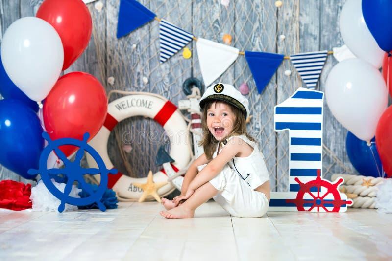 O capitão pequeno senta-se no assoalho em um estilo marinho Nós marcamos o primeiro ano imagem de stock royalty free