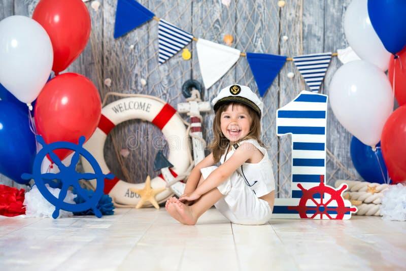 O capitão pequeno senta-se no assoalho em um estilo marinho Nós marcamos o primeiro ano imagem de stock