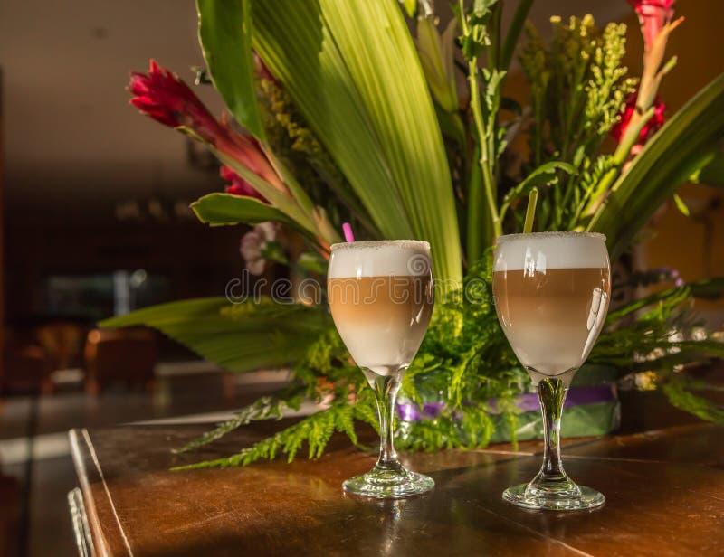 O cappuccino fresco no vidro de vinho que está na sala na tabela de madeira do vintage velho, iluminada com luz solar da manhã ir foto de stock