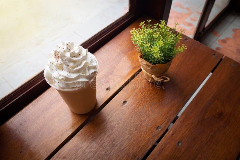 O cappuccino mistura dentro o copo plástico Servido na tabela de madeira no café Menu favorito da bebida da cafeína imagens de stock