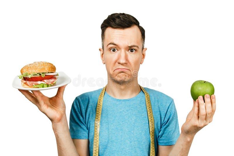 O cara com fita de medida segura hambúrguer e maçã verde Conceito de escolha entre alimentos saudáveis e não saudáveis imagens de stock royalty free
