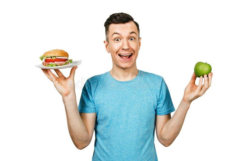 O cara segura maçã verde e um hambúrguer sobre fundo claro Conceito de escolha entre fast food saudáveis e não saudáveis foto de stock