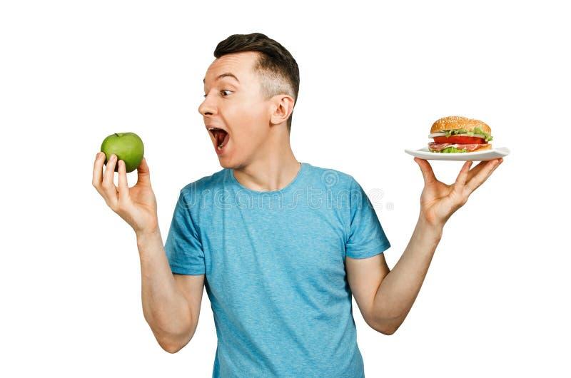 O cara segura maçã verde e um hambúrguer sobre fundo claro Conceito de escolha entre fast food saudáveis e não saudáveis imagem de stock