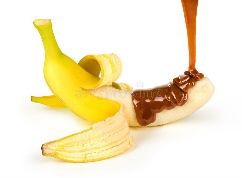 O caramelo é derramado em uma banana foto de stock royalty free