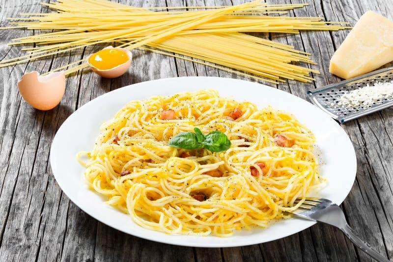O carbonara dos espaguetes, manjericão, gema de ovos, raspou o queijo parmesão, b imagens de stock