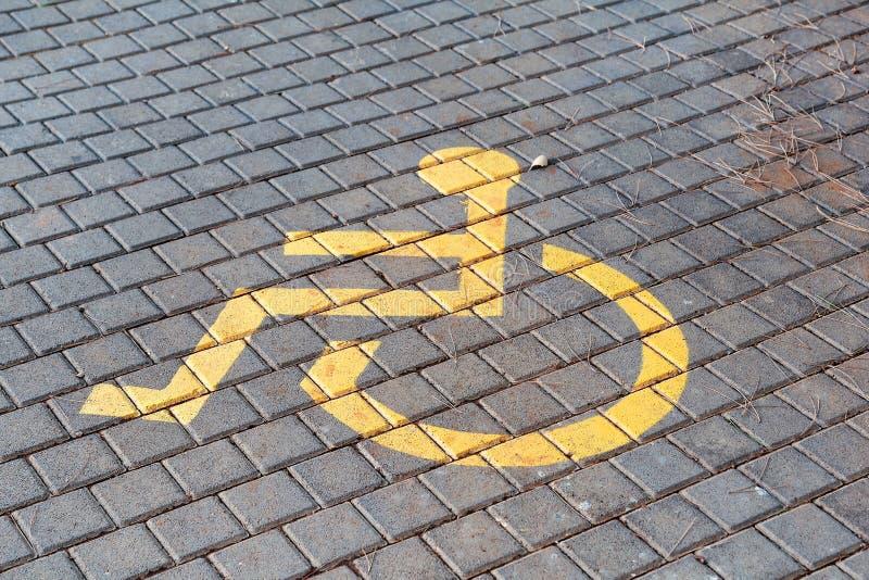 O cargo com lugar de estacionamento deficiente e o sinal na frente da baía de estacionamento no parque de estacionamento/marcaram fotografia de stock royalty free