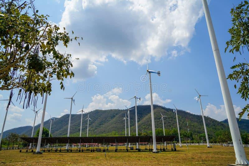 O cargo e a célula solar brancos do moinho de vento almofadam a tecnologia para gerar a energia renovável limpa na jarda da grama fotos de stock royalty free