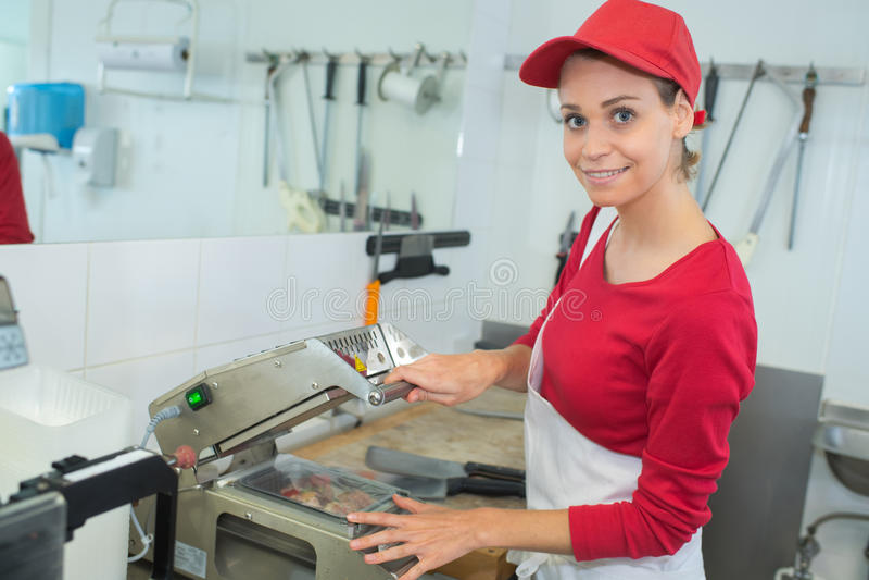 O carniceiro da carne dos cortes do trabalhador que segura a escolha principal dos cortes corta foto de stock