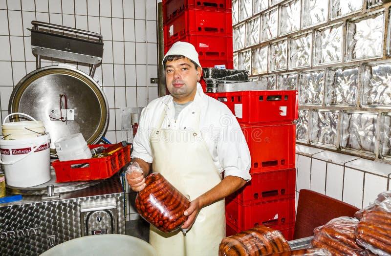 O carniceiro prepara a salsicha fresca fotografia de stock