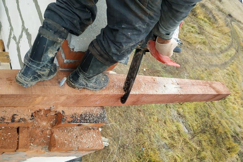 o carpinteiro com uma serra de cadeia faz bebeu em uma construção do feixe de madeira das casas fotos de stock