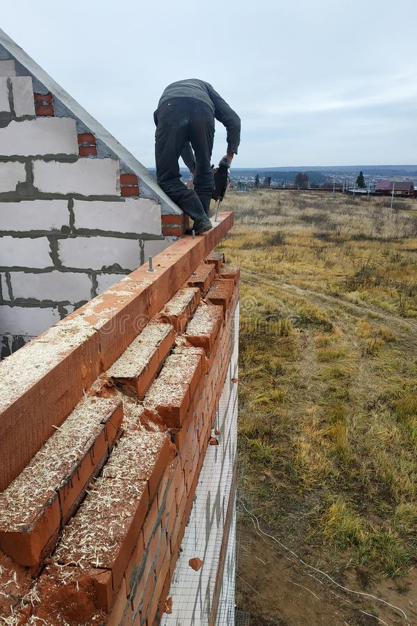 o carpinteiro com uma serra de cadeia faz bebeu em uma construção do feixe de madeira das casas foto de stock