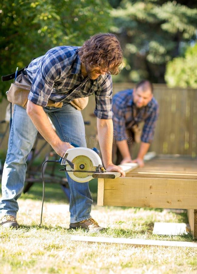 O carpinteiro Cutting Wood With Handheld viu quando imagem de stock