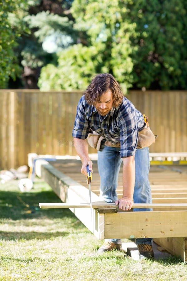O carpinteiro Cutting Wood With viu na construção fotografia de stock royalty free