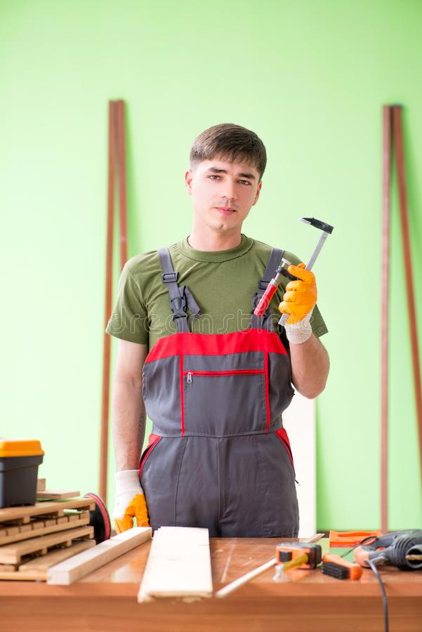 O carpinteiro do homem novo que trabalha na oficina fotos de stock royalty free