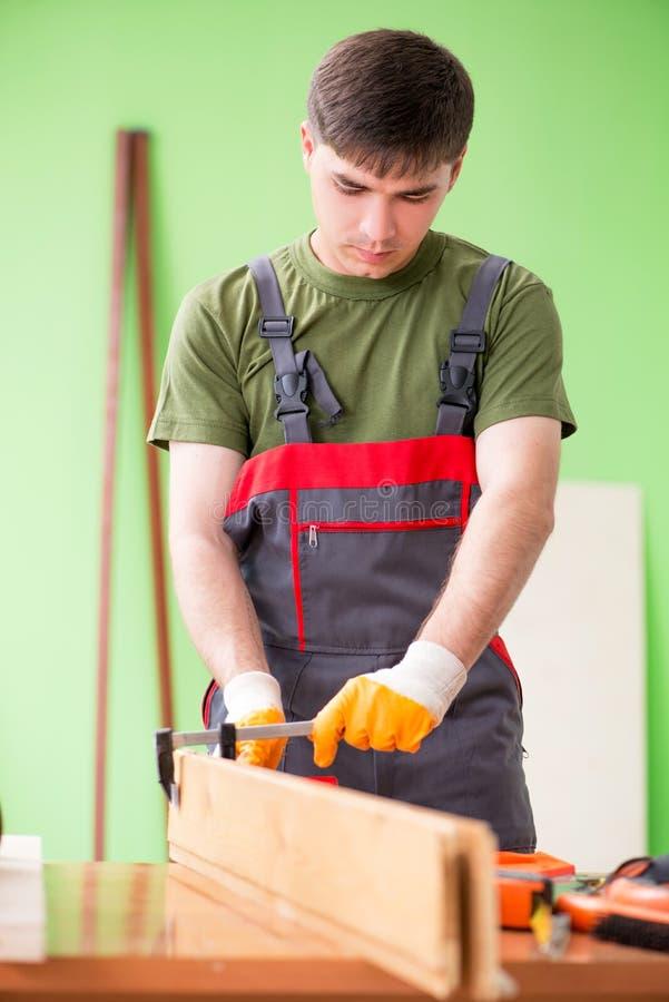 O carpinteiro do homem novo que trabalha na oficina imagem de stock royalty free