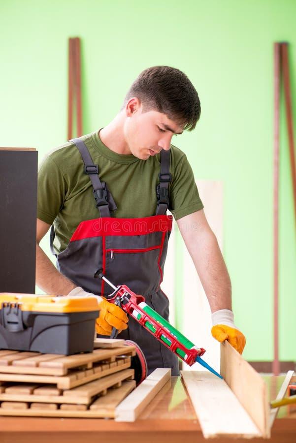O carpinteiro do homem novo que trabalha na oficina imagem de stock