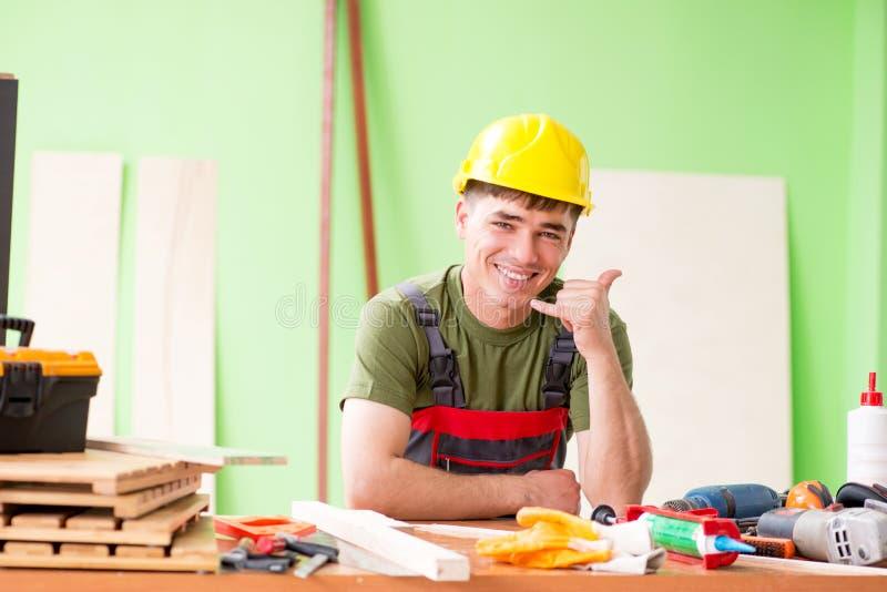 O carpinteiro do homem novo que trabalha na oficina imagens de stock royalty free