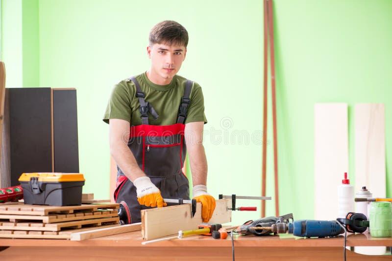 O carpinteiro do homem novo que trabalha na oficina fotografia de stock