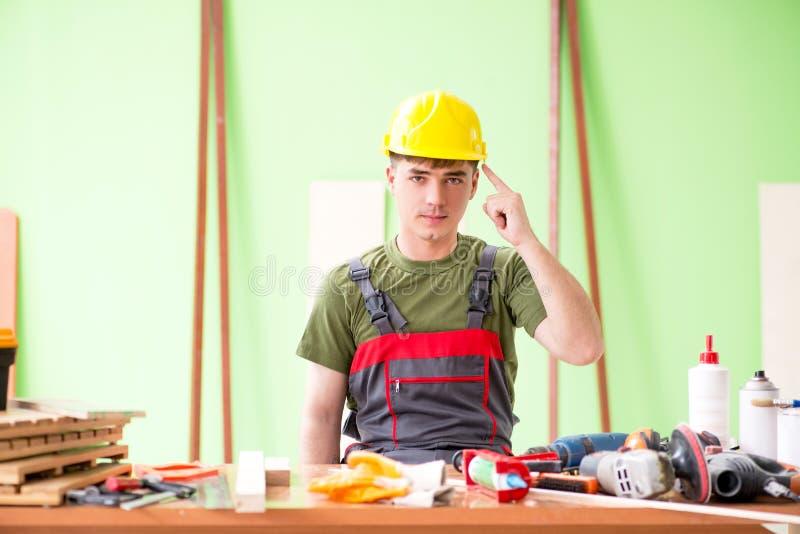 O carpinteiro do homem novo que trabalha na oficina foto de stock