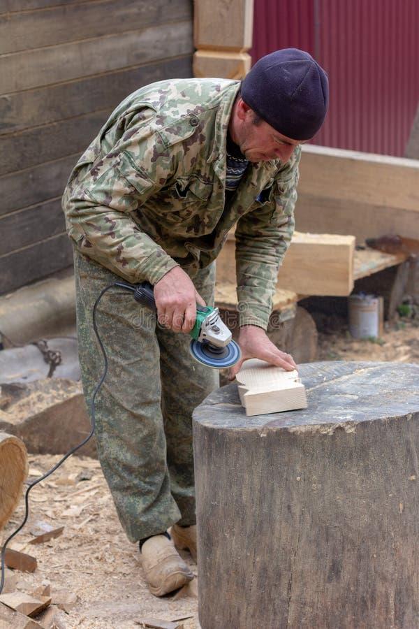 O carpinteiro do marceneiro segura o detalhe de madeira do moedor imagens de stock