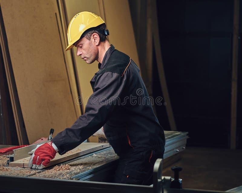 O carpinteiro está inclinando-se na tabela de madeira fotografia de stock royalty free