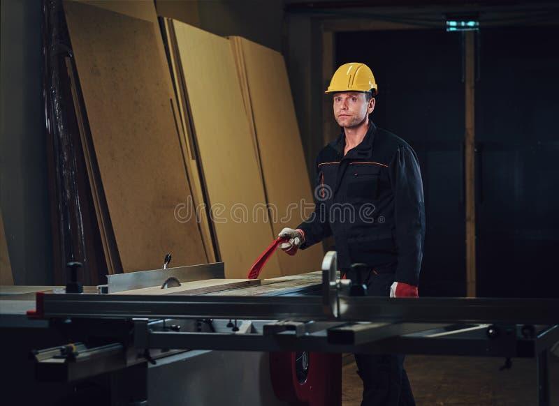 O carpinteiro está inclinando-se na tabela de madeira imagens de stock